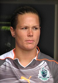 A head-and-shoulders photograph of Ashlyn Harris, a white woman in her mid-20s, dressed in a predominately grey soccer uniform with orange piping; she is looking to her left.