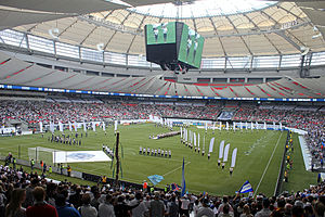 Row of people with white flags stand on a soccer field inside of a stadium. People watch from their seats, which surround the field.