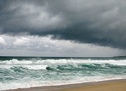 A beach is battered by choppy seas from an offshore storm and overcast, dark skies hang overhead.