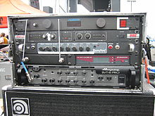 An equipment rack from a modern bass player's performance system is shown. Several electronic devices are mounted onto the equipment rack.