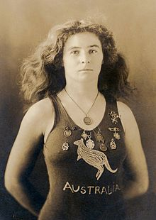 "A sepia-toned photograph taken from the waist up, showing a white woman of medium build with shoulder-length wavy hair, wearing a one-piece swimming costume with the word ""AUSTRALIA"" on the front and a depiction of a kangaroo. She has nine medals pinned to costume around the upper chest area, and is wearing another medal around her neck."