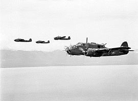 Four twin-engined military aircraft in low-level flight over the ocean