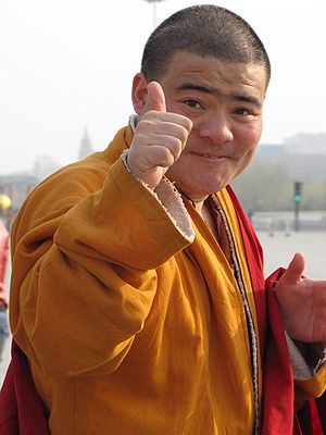 Thumb signal - A Chinese Buddhist monk giving the common thumbs up sign of approval
