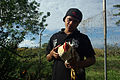 Bethesda student Peter holds one of the local chickens they are learning to keep. (10677068804).jpg