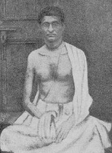 A young skinny Indian man sitting with chanting beads in hand