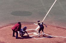 A view of home plate from the first base side seats. A left-handed batter with the number 48 on his black uniform is in the batter's box looking down at home plate with one hand on the bat which is resting on his shoulder. The catcher in a white uniform has just caught a ball close to the ground. The umpire, wearing blue pants and a red jacket, is leaning over the catcher.