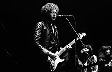 Dylan, onstage and with eyes closed, plays a chord on an electric guitar.