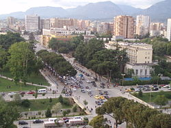 The boulevard crossing from west to east at the lower portion of the picture, passing the Skanderbeg Square.
