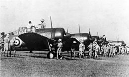 Row of single-engined military monoplanes parked on an airfield