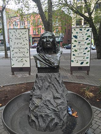 Lushootseed - Bust of Chief Seattle with accompanying text in Lushootseed: ti šišəgʷł gʷəl al tiʔəʔəxʷ sgʷaʔčᵉł səxʷəsłałlilčəł siʔał dəgʷi gʷəl liiiiləxʷ dʔiišəd cəłul'ul' cəł ʔəslax̌ədxʷ ti gʷaalapu