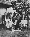 COLLECTIE TROPENMUSEUM Portret van een rouwende Ambonese familie met een gestorven kind in hun midden offers en bloemen TMnr 60043322.jpg
