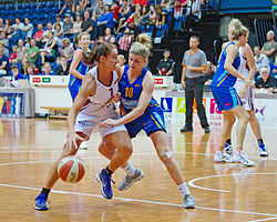 A female basketball player is attempting to drive to a basket while another female player is guarding her, and attempting to reach for the ball.