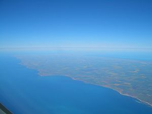 "Yorke Peninsula - Aerial view of Yorke Peninsula, looking south from around Ardrossan. Gulf St Vincent is in the foreground, Spencer Gulf in the background. The ""foot"" of the ""boot"" can be discerned near the horizon"