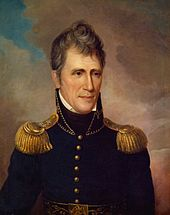 A man with graying, wavy hair wearing a high-collared black military jacket with gold epaulets and buttons