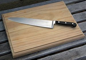 This is a wooden chopping board with a chef's ...