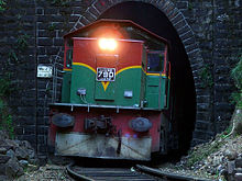 Red-and-green locomotive emerging from a tunnel