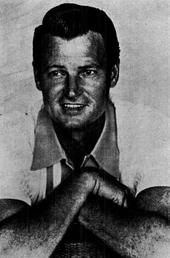 A dark-haired man wearing a casual shirt, with his arms folded in front of him
