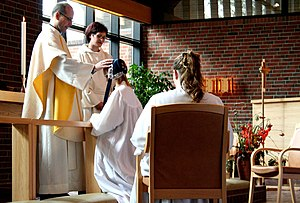 A girl is blessed by the priest during her con...