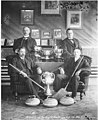 Curling team sitting around trophies, brooms, and stones, Dawson, Yukon Territory, 1905 or 1906 (AL+CA 1401).jpg
