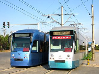 "Trams in China - Dalian modern tram. Tram type DL6WA, mark Dalianren (meaning ""Dalian people"") manufactured by Tram Factory of Dalian Public Transport Group. The blue one is manufactured in 2009, the other in 2001–2003."