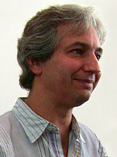 Portrait de David Shore souriant en conférence de presse.