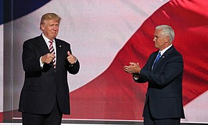 "Donald Trump and his running mate for vice president, Mike Pence, at the Republican National Convention in July 2016. They appear to be standing in front of a huge screen with the colors of the American flag displayed on it. Trump is at left, facing toward the viewer and making ""thumbs-up"" gestures with both hands. Pence is at right, facing toward Trump and clapping."