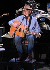 A grey-haired man with a beard wearing a cowboy hat, blue shirt and jeans, playing a guitar and singing into a microphone