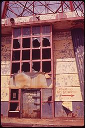 An abandoned entrance building to the abandoned Parachute Jump, seen in 1973. Several windows are broken and the paint has started to peel.