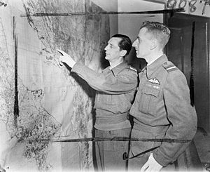 William Elliot (RAF officer) - Air Vice Marshal W Elliot, the former Air Officer Commanding the Balkan Air Force (left), gives the latest information regarding Balkan operations to his successor, Air Vice Marshal George Mills (right) at BAF Headquarters, Bari, Italy, 1945