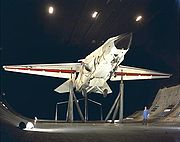A F-111B on support inside a large wind tunnel