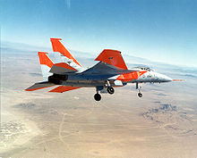 Jet aircraft with distinctive orange markings banking left over desert, with landing gears extended.
