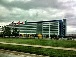 A wide rectilinear six-story blue-and-white building with the American, Canadian and Mexican flags flying in front, seen from a nearby roadway, under a cloudy sky