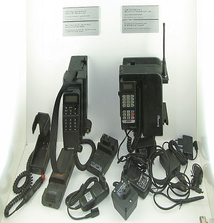 Two 1991 GSM mobile phones with several AC adapters GSM-Telefone-1991.jpg
