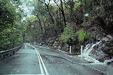 Water sluicing across Galston Gorge Road during rain