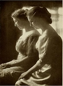 Black and white image of two women with their heads bowed and hands in their lap. They're both wearing dresses and have their hair pinned back.