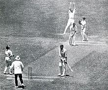 A cricketer has just been caught and bowled, surrounded by some fielders