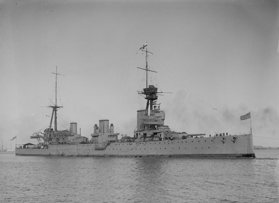 Side view of a large warship with three funnels and two large masts at rest on flat water.