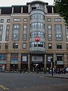 "A beige building with a circular, red sign in the middle stating ""Coca-Cola"" in white letters and a rectangular, blue sign below"