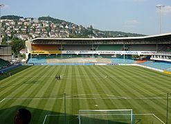 Vue d'un stade de football aux tribunes vides avec une colline et des maisons en arrière-plan