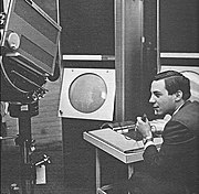 A young man sits holding a microphone in his left hand while manipulating the console of an apparatus with his right. To his left a large television camera is trained on a large, circular cathode ray tube display.