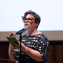 Half-length portrait of Helen Zaltzman speaking into a microphone