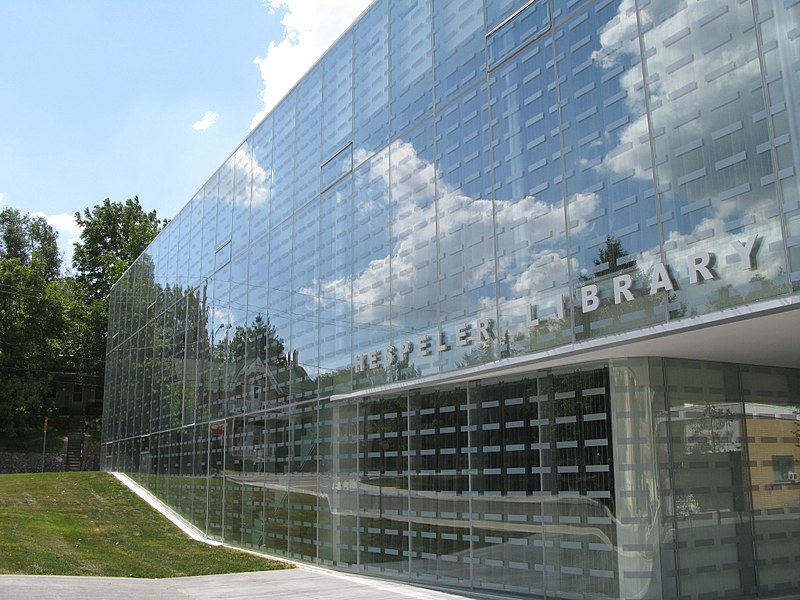 The new Hespeler Library in Cambridge, Ontario was built by constructing a glass cube around the historic Carnegie library; Obtained from Wikimedia Commons under the terms of the GNU Free Documentation License.