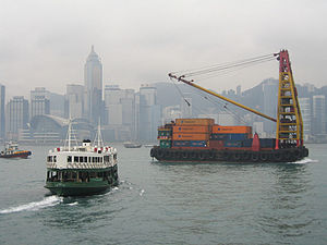 Lighter (barge) - A lighter carrying shipping containers (loaded and unloaded by the tall derrick-crane on the lighter's top-deck) in Hong Kong's Victoria Harbour.