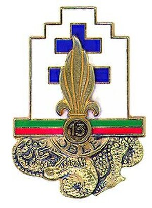"13th Demi-Brigade of Foreign Legion - Regimental Insignia of the 13th Demi-Brigade of the Foreign Legion, 1st Model ""drakkar on the waves, surrounded from one part to another by the motto MORE MAJORUM in golden letters and underlined by a legion grenade seal with ""13"", all on a white background"""
