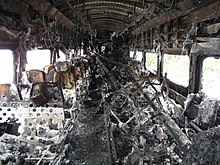 A rail passenger car interior with no upholstery, showing many burn marks and other fire damage. Several long pieces of metal are piled in the center near the back end of the car.