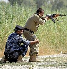 Sotilas vakauttamassa toista sotilasta, joka ampuu kivääriä