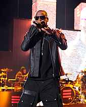 A man dressed in black rapping in front of a band