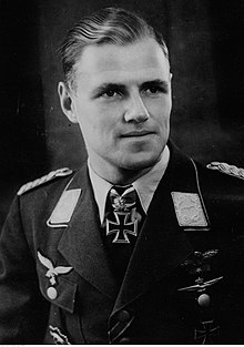 A black and white photo of the head and shoulders of a young man. He wears a peaked cap and military uniform with an Iron Cross displayed at the front of his shirt collar.