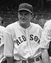 "A smiling man wearing a white baseball uniform with ""RED SOX"" across the chest and a dark baseball cap"