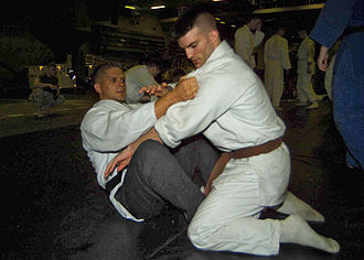 Guard (grappling) - The butterfly guard being used during Judo training. The judogi of the top combatant is grabbed to prevent him from moving away.
